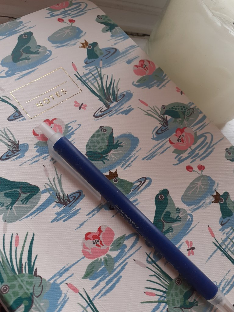 A notebook with pen resting on it, ready to write